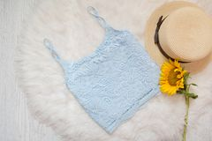 Blue lace top, straw hat and sunflower. On white fur, top view.  Stock Photo