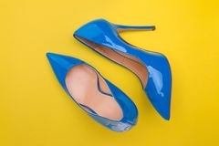 Blue lacquered high-heeled shoes. Blue patent leather shoes on a yellow background royalty free stock image