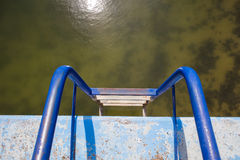 Blue ladder in dirty swimming pool Royalty Free Stock Image