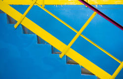 Blue ladder with yellow railing, background Royalty Free Stock Images