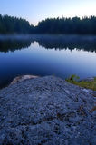 Blue Lagoon. A misty blue lake during the morning sunrise in northern Ontario.  Waters and trees in background all blurred with rocky foreground in focus Royalty Free Stock Photos