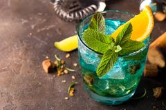 Blue Lagoon cocktail with ice, mint and slice orange on dark stone background, close up stock photos