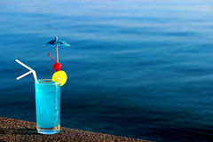 Blue lagoon cocktail on water background. Alcohol cocktail with with cherry, ice and lime by the water Stock Photo