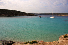Blue lagoon on the Comino Island, Malta. The Blue Lagoon on the tiny island of Comino with Gozo in the distance. Malta Stock Photography