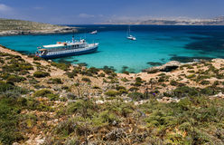 Blue Lagoon - Comino - Malta. The Blue Lagoon on the tiny island of Comino with Gozo in the distance in the Mediterranean islands of Malta stock photo