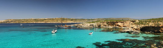 Blue Lagoon - Comino - Malta. Panoramic view of Exotic waters in the Blue Lagoon on the tiny island of Comino with Gozo in the distance in the Mediterranean Stock Image