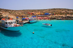 Blue Lagoon - Comino, Malta. View of Blue Lagoon at Comino Island near Malta. Crystal clear sea water, cruise ships and people at beach Stock Photography