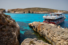BLUE LAGOON, COMINO, MALTA - APRIL 13, 2016. People arriving with a ferry to this blue lagoon  with crystal clear blue waters. Blue Lagoon on a sunny day in Stock Image