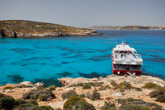 BLUE LAGOON, COMINO, MALTA - APRIL 13, 2016. People arriving with a ferry to this blue lagoon  with crystal clear blue waters. Blue Lagoon on a sunny day in Stock Photo