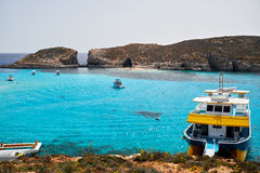 BLUE LAGOON, COMINO, MALTA - APRIL 13, 2016. People enjoy blue lagoon  with crystal clear blue water. Royalty Free Stock Photography