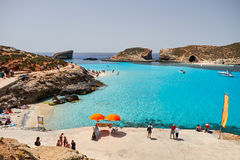 BLUE LAGOON, COMINO, MALTA - APRIL 13, 2016. People enjoy blue lagoon  with crystal clear blue water. Royalty Free Stock Photo