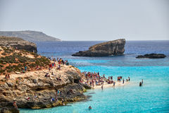 BLUE LAGOON, COMINO, MALTA - APRIL 13, 2016. People enjoy blue lagoon with crystal clear blue water. Blue Lagoon on a sunny day in APRIL 13, 2016 in Comino Stock Images