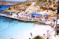 The Blue Lagoon, Comino, Malta. The beach and sundeck with holidaymakers sunbathing at the Blue Lagoon, Comino, Malta Stock Images