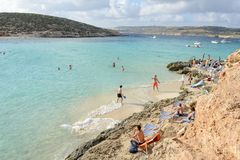 Blue Lagoon on Comino in Malta. Comino, Malta - 30 October 2017: people swimming and sunbathing at Blue Lagoon on Comino in Malta Royalty Free Stock Photo