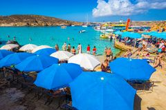 BLUE LAGOON, COMINO, MALTA - October 18, 2016: Tourists crowd to enjoy the clear turquoise water under umbrellas on a sunny day. In October 18, 2016 in Comino Royalty Free Stock Images