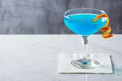 Blue Lagoon or Blue Hawaii Cocktail with Twist. A chilled cocktail, either a Blue Lagoon, Blue Hawaii, or some other mysterious blue beverage in a glass goblet Royalty Free Stock Images