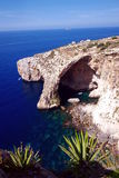 Blue Lagoon of Malta. The Blue Lagoon of Malta, beautiful clear water of the Mediterranean Sea and the cliffs and cave and grotto with small boats going around Stock Image