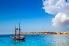 Blue Lagoon, Malta - Old sailing boat at the Island of Comino next to the famous Blue Lagoon. With the Island of Gozo and town of Mgarr at the background on a Stock Photos