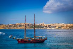 Blue Lagoon, Malta - Old sailing boat at the Island of Comino next to the famous Blue Lagoon with the Island of Gozo. And town of Mgarr at the background on a Royalty Free Stock Photography