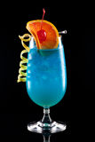 Blue Lagoon - Most popular cocktails series. Bright Blue Lagoon cocktail over black background on reflection surface, garnished with orange slice, maraschino Royalty Free Stock Images