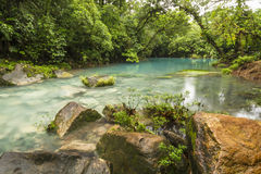 Blue Lagoon and Orange Rock. The cerulean blue waters of the 'Blue Lagoon' on the Rio Celeste in Volcan Tenorio National Park, Costa Rica Stock Photography