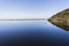 Blue Lagoon Water Paddler Landscape. Blue lagoon river glass smooth water with distant sup paddler on board on rural scenic coastline  landscape Stock Photos