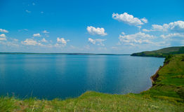 Blue lake. Summer landscape with quiet water of lake and cloudy sky Royalty Free Stock Photos