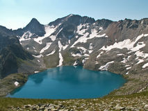 The Blue lake. A blue lake surrounded by mountains, snow and green grass. The image was made at the altitude of 3000 m above sea level Stock Image