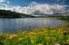 Blue lake. Fnd yellow flowers Stock Photo