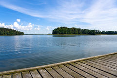 Blue Lake. View at the forest from the wooden pier on lake. Blue cloudy sky Royalty Free Stock Photo