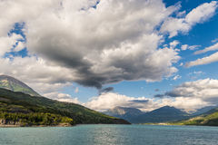 Blue lake amid mountain range and dramatic sky in idyllic uncontaminated environment once covered by glaciers. Dramatic sky, summe. R season, wide angle view Royalty Free Stock Image