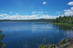 Beautiful lake in Sweden with deep blue water and a nice blue sky with white clouds stock image