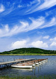 Blue lake with boats and cloudy sky Stock Photo