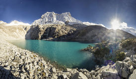 Blue lake in foot of snow-covered mountain at sunrise Royalty Free Stock Photography