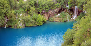 Blue lake with forest and waterfall. Picturesque landscape picture from Plitvice lakes, Croatia with summer green trees in the forest and a wonderful waterfall Stock Photos