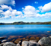 Blue lake idill under cloudy sky Royalty Free Stock Photography