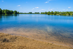 Blue Lake II. Clear blue lake - bright day - few clouds Royalty Free Stock Photography
