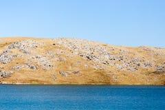 Blue lake near yellow rocks in nature Stock Image