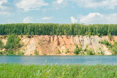 Blue lake with the orange yellow sand hills mountain and forest on top against sky.  Stock Image
