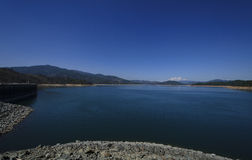 Blue Lake and Sky at a Dam. A view of dam that has vivid blue lake and a stunning blue sky with mountains in the distance Royalty Free Stock Images