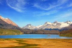 A  blue lake and snow-capped mountains. A  blue lake in a picturesque valley surrounded by snow-capped mountains. National Park Perito Moreno  in Patagonia Stock Photos