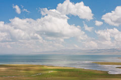 Blue lake Son Kul in Kyrgyzstan under white clouds. Panorama with lake and blue cloudy sky above on a clear day Stock Photo