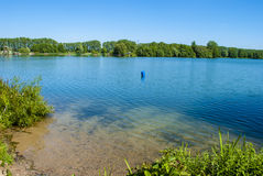 Blue Lake. In spring (in Germany) - bushes and trees all around - clear blue sky with no clouds Stock Photography