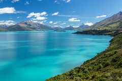 Blue lake surrounded by mountains Royalty Free Stock Images