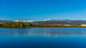 Blue lake under the bright blue sky. Blue lake under a bright blue sky surrounded by mountains Royalty Free Stock Images
