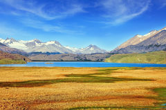 The blue lake in valley surrounded by snow-capped mountains. Royalty Free Stock Image