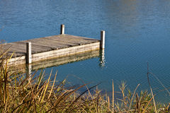 Blue lake waters and wooden jetty with clear reflection in a fal Stock Photo