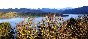 Blue lake and  white Sky in Wide Frame. Tree in warm color by sunset at foreground.Blue Mountain at faraway Stock Photo