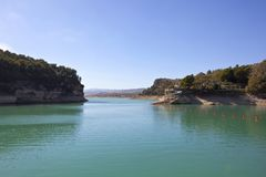 Blue lake and woodlands in the mountains of Andalucia. A calm blue lake with rocky cliffs and woodland with a villa and jetty under a blue sky in andalucia spain royalty free stock images