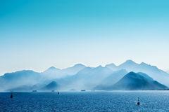 Blue Is(Land). Where the sky falls into the water over the mountains Stock Image